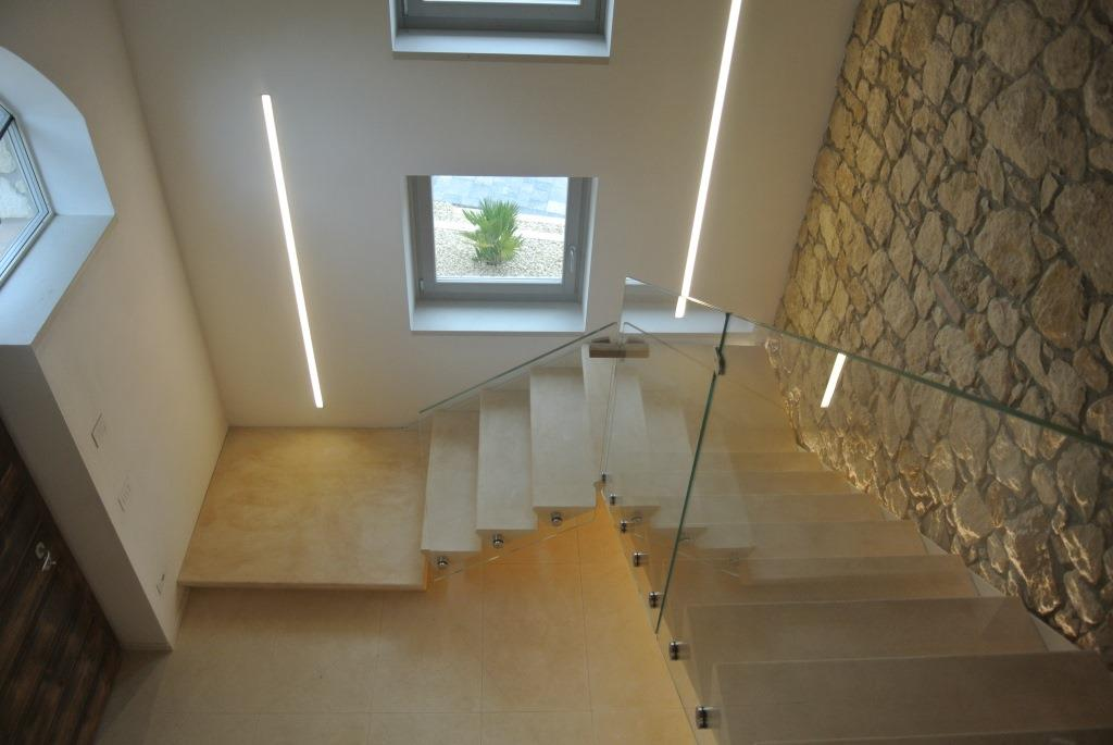 Scala composta da gradini a massello posati su un trave in acciaio verniciato e parapetto in vetro