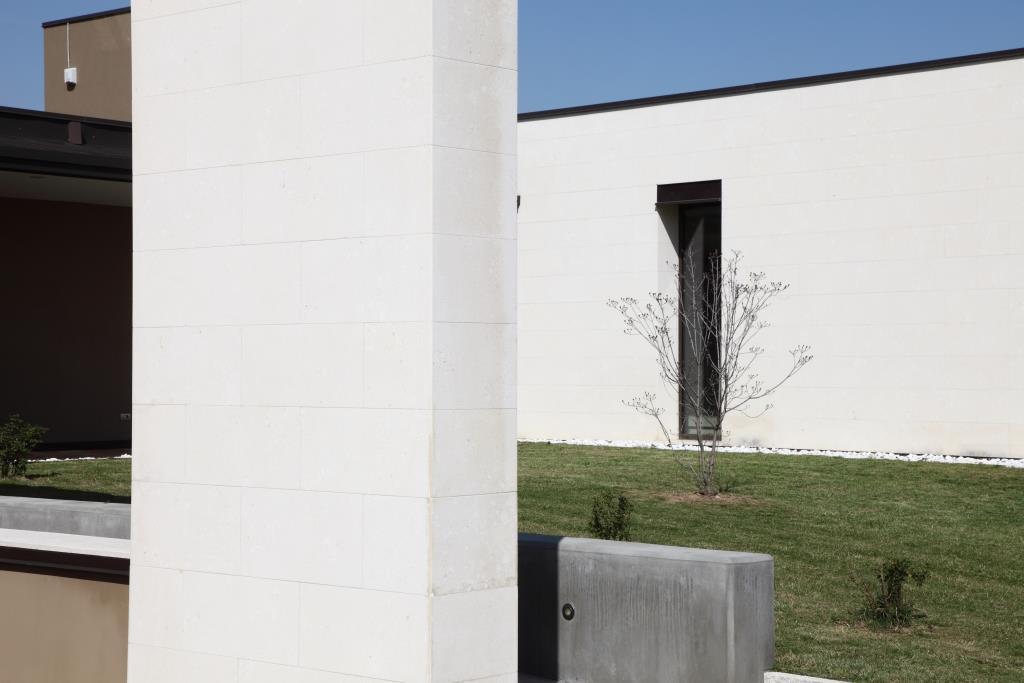 Rivestimento in pietra bianca posato a colla su muro rasato