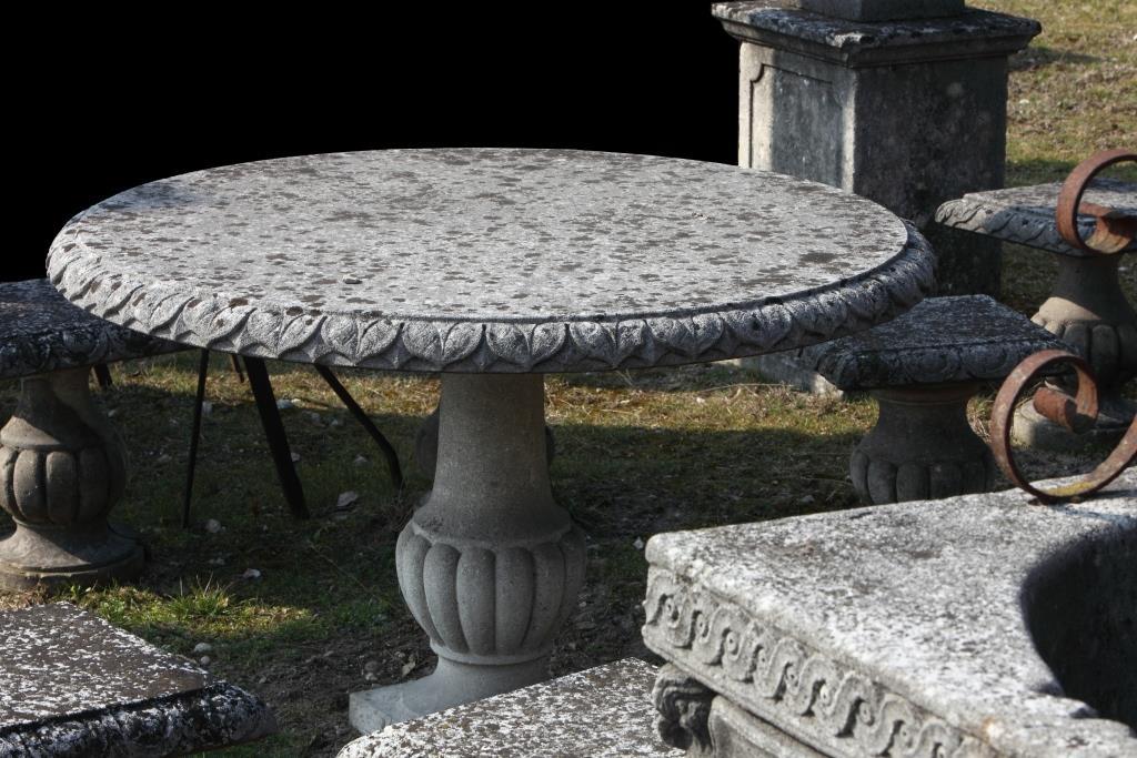 Tavolo rotondo con bordo scolpito con foglie e base con bugne in pietra di Vicenza