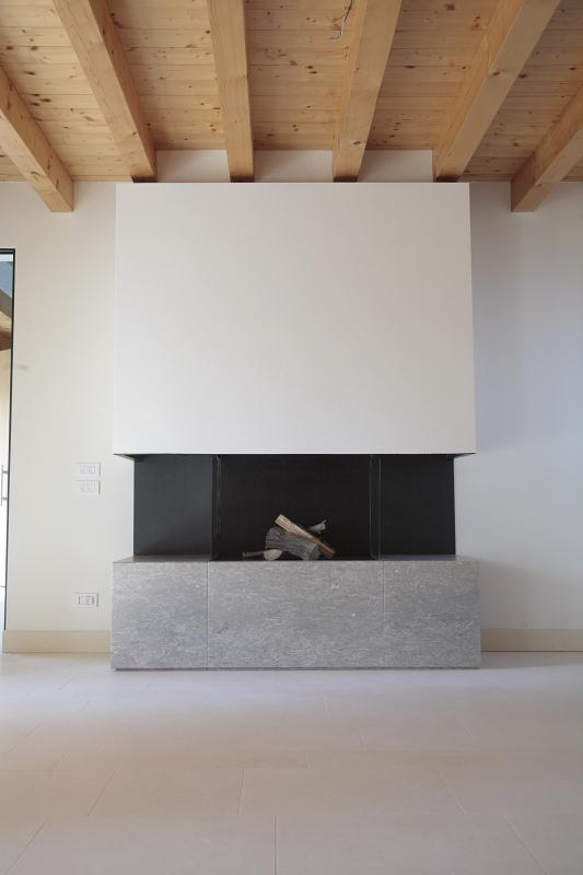 Caminetto con focolare in pietra di Vicenza grigia e bocca di fuoco in metallo verniciato
