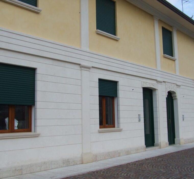 Rivestimento facciata intervallato da lesene e fregi scolpiti in pietra di Vicenza