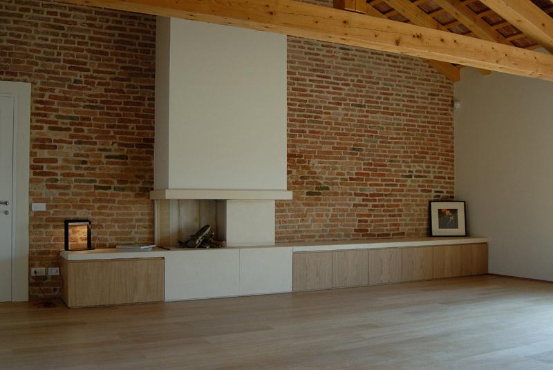 Parete zona tv con camino in pietra di Vicenza e cassettoni in legno