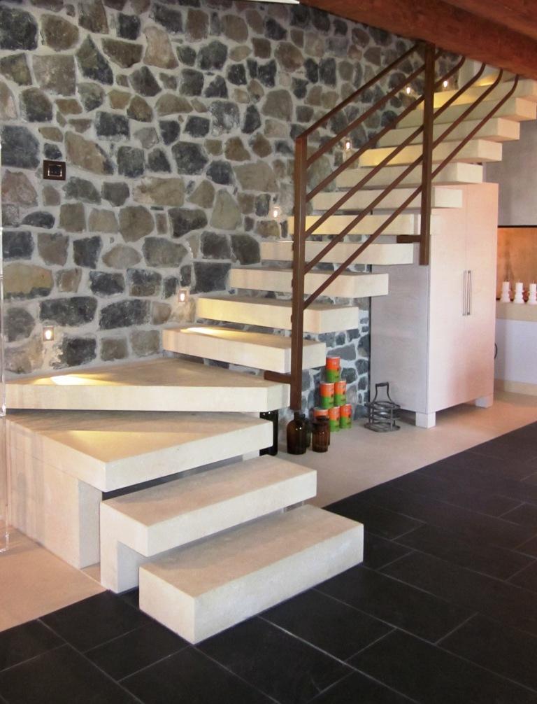 Scala in pietra Palladio Bianca composta da gradini a massello a giorno autoportanti inseriti nel muro di sassi a vista