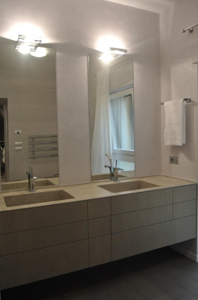 Piano lavabo a massello spessore cm 12 con lavabo scavato, bordo frontale smussato a 45° per un effetto a scomparsa e bordo perimetrale sul muro ricavato ribassando il piano.
