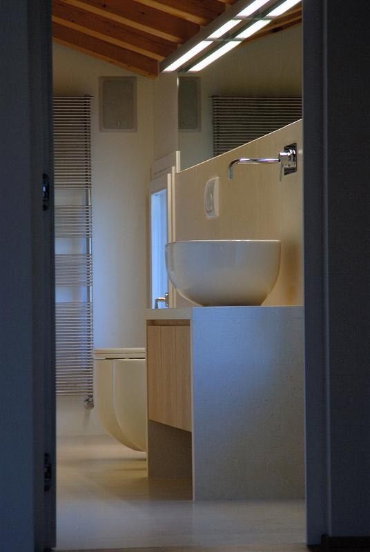 Rivestimento, pavimento in pietra bianca, con panca per lavabo in pietra e cassettone in legno.