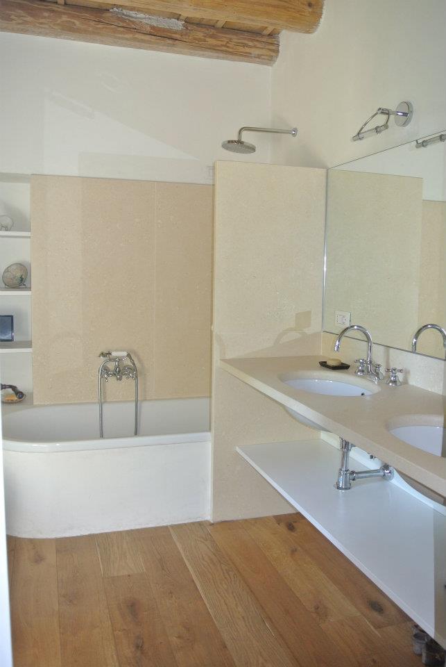 Bagno con rivestimento, piano lavello e muretto divisorio doccia in pietra bianca e pavimento in listoni legno spazzolato.