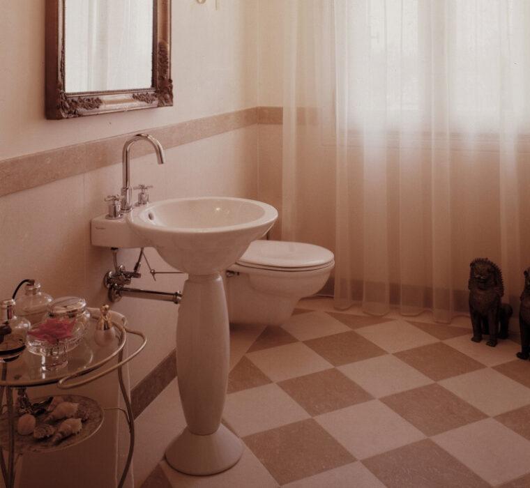 Bagno con boiserie in legno laccato, rivestimento vasca e pavimento in pietra bianca e gialla.