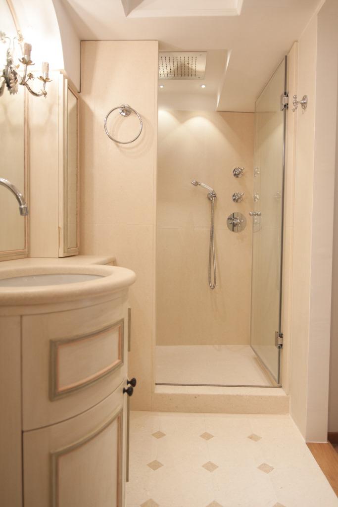 Rivestimento pareti, piatto doccia e piano lavello in pietra bianca con pavimento in pietra bianca e tozzetti in pietra gialla.