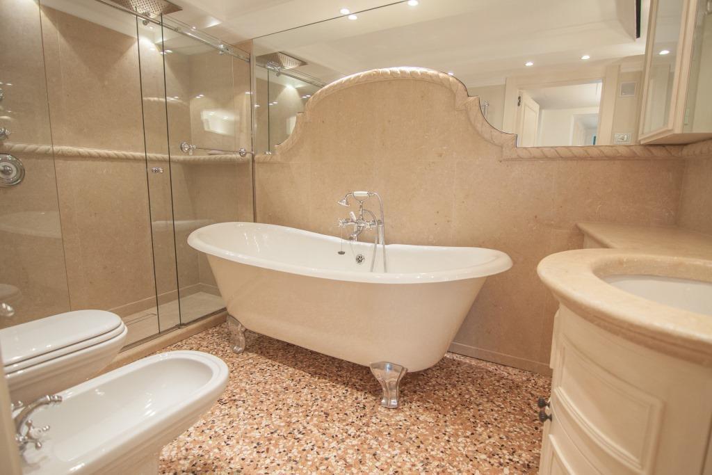 Bagno con rivestimento, piatto doccia e piano lavabo in pietra gialla con bordo scolpito con motivo a corda in pietra gialla.