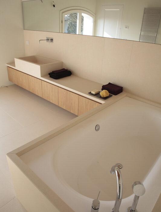 Rivestimento pareti e vasca, pavimento e lavabo in pietra bianca.
