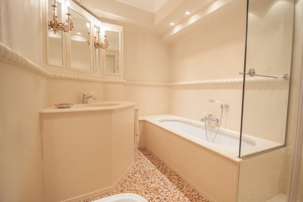 Bagno con rivestimento, piani e bordo scolpito con motivo a corda in pietra bianca.