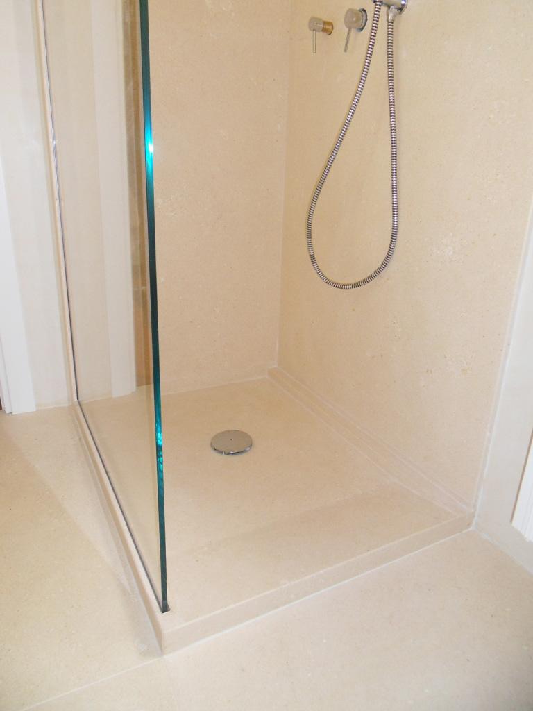 Rivestimento e piatto doccia in pietra bianca con lastra in vetro inserita nella pietra129 bagno con rivestimento, pavimento, piatto doccia a filo pavimento in pietra bianca e blocco lavello a massello in pietra grigia, vetro divisorio doccia con specchio inserito.
