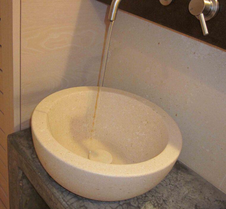 Ciotola lavabo in pietra bianca con panca per lavabo in cemento rasato e resinato.