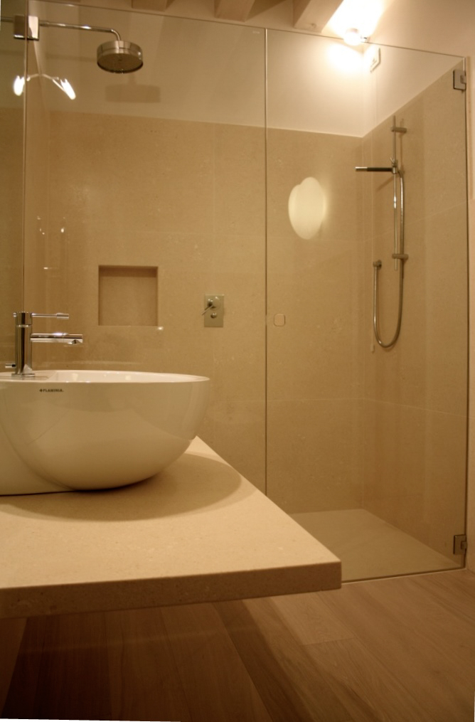 Bagno con rivestimento e piano lavabo in pietra e pavimento in legno, piatto doccia in pietra a filo pavimento.